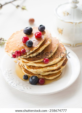 Stack of pancakes with berries drizzled with maple syrup on white plate on white table, close up - stock photo
