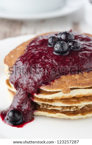 stack of pancakes with black currant jam on a plate closeup - stock photo