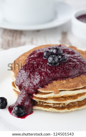 stack of pancakes with black currant jam on a white plate - stock photo