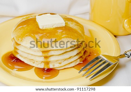 Stack of pancakes with butter, maple syrup, and fork.  Coffee in background. - stock photo