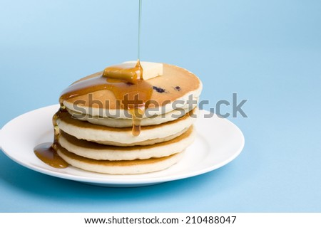 Stack of pancakes with maple syrup and butter - stock photo