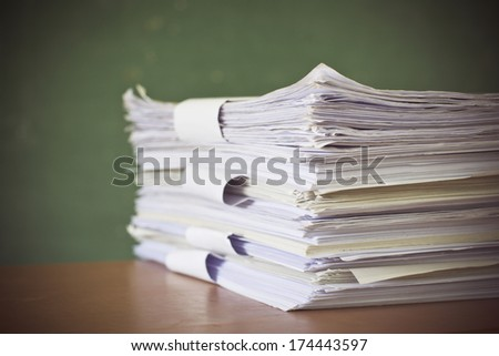 stack of paper on blackboard - stock photo