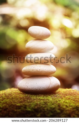 Stack of pebble stones by a stream in a forest at sunset - stock photo