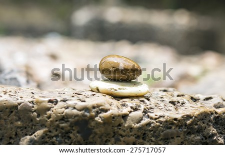 Stack of pebble stones by a stream , river background - stock photo
