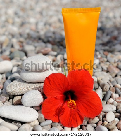 Stack of pebbles, cream and flower at the beach - stock photo