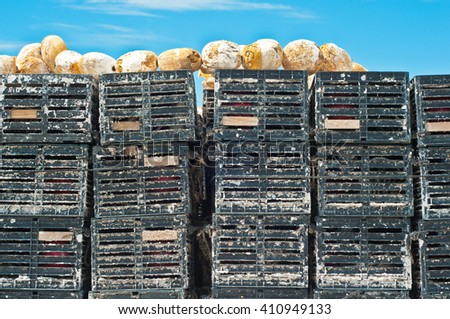 Stack of plastic crab traps and buoys drying in the sun - stock photo