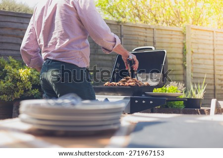 Stack of plates on a table outside in a garden with a man attending to a barbecue in the background - stock photo
