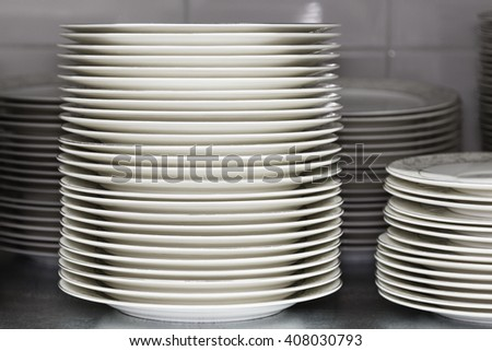 Stack of plates on the showcase. Restaurant utensils. Shallow focus - stock photo