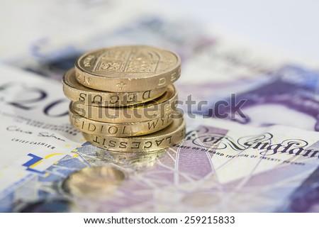 Stack of Pound Coins on Twenty Pound Notes - stock photo