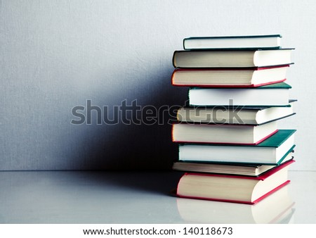 Stack of red, green and black books on white reflective surface - stock photo
