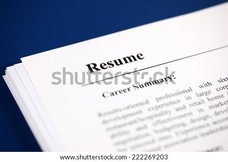 Stack of resumes on a blue background. - stock photo