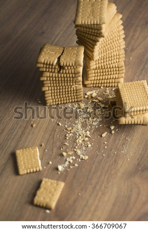 Stack of several sweet rectangle crisp cookies on wooden table - stock photo