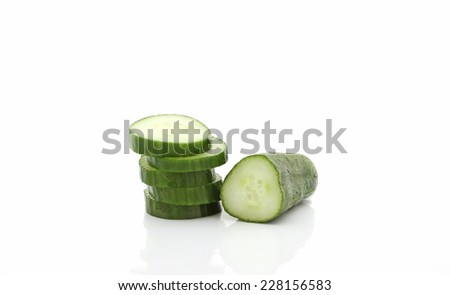 Stack of sliced cucumbers and half cucumber isolated over white background. - stock photo
