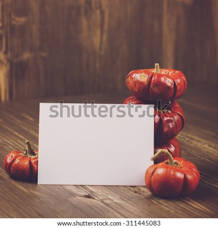 Stack of small orange decorative pumpkins with a card for text. Halloween or thanksgiving day concept. Vintage style, selective focus. Toned square image - stock photo