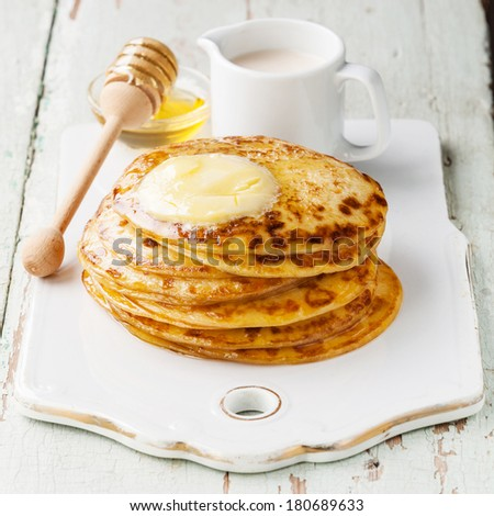 Stack of Small pancakes with butter and honey - stock photo