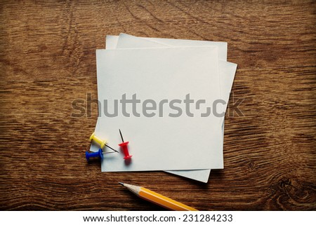 Stack of small square blank white memo pages with a pencil for jotting notes and reminders and thumbtacks to attach to a notice board, overhead view on a wooden desk - stock photo