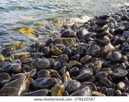 Stack of smooth stones on a seashore, Beach and rock stack - stock photo
