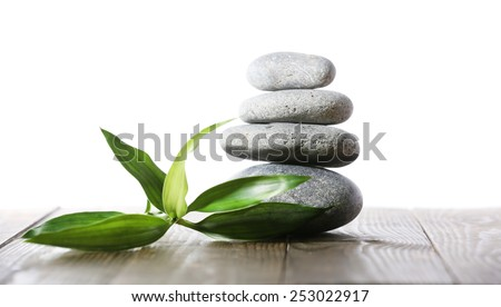 Stack of spa stones on wooden planks surface isolated on white - stock photo