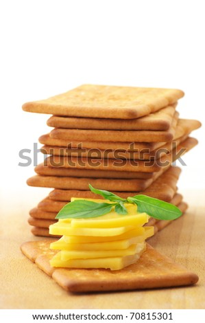 Stack of square crackers with slices of cheese and basil on wooden board against white background. - stock photo