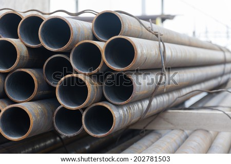 Stack of steel pipes on warehouse - stock photo