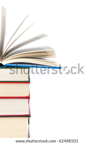 Stack of three books with a fourth open lying on top - stock photo