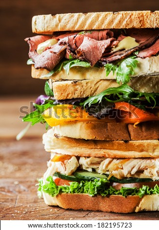 Stack of three delicious toasted sandwiches with different fillings including rare roast beef,shredded chicken breast and pepper and cheese all garnished with herb and salad ingredients,close up view - stock photo