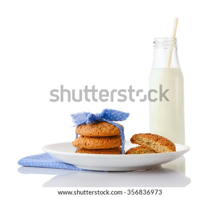 Stack of three homemade oatmeal cookies tied with blue ribbon in small white polka dots and halves of cookies on white plate on napkin and bottle of milk with straw, isolated on white background - stock photo