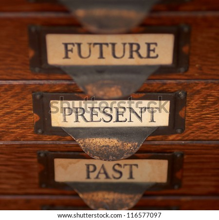 "Stack of three old, oak flat file drawers with ""PAST"", PRESENT, and ""FUTURE"" printed on tags in tarnished brass label holders. Shallow depth of field with focus on ""PRESENT"". - stock photo"