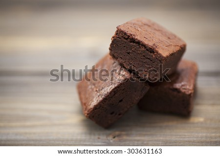 Stack of three pieces of chocolate brownie cake on a wooden background. - stock photo