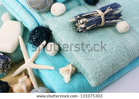 Stack of towels, soaps, starfish, shells on gray background. - stock photo