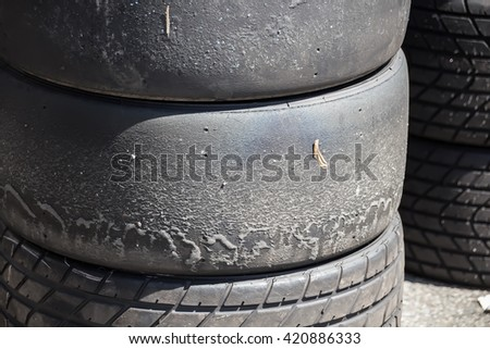 Stack of used race slicks and good looking rain tires. The sllicks are allready worn from the race or traing session. - stock photo