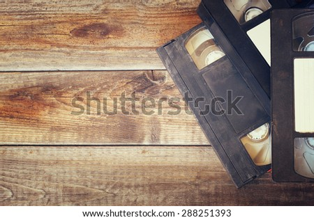 stack of VHS video tape cassette over wooden background. top view photo. retro style image - stock photo