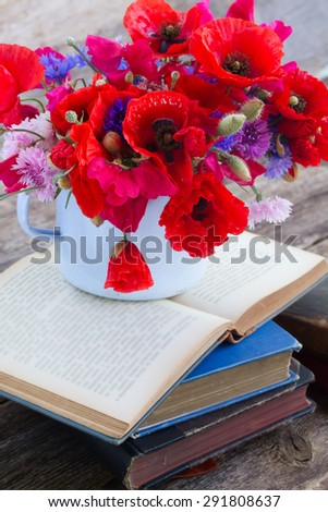 stack of vintage old books  on table with fresh field flowers - stock photo