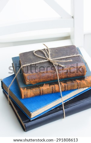 stack of vintage old books  on white chair - stock photo