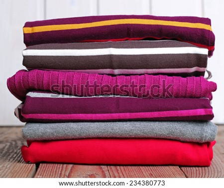 Stack of warm knitting clothing lying on a wooden table - stock photo