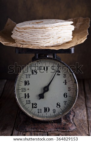Stack of wheat tortillas on old vintage kitchen scales - stock photo