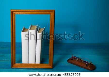 Stack of white books, grungy blue background, free copy space. Vintage old hardback books on wooden shelf, deck table, no labels, blank spine. Back to school, Case and glasses - stock photo