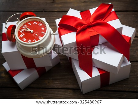 Stack of white Christmas presents on dark wooden background - stock photo