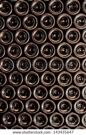 Stack of wine bottles in winery - stock photo