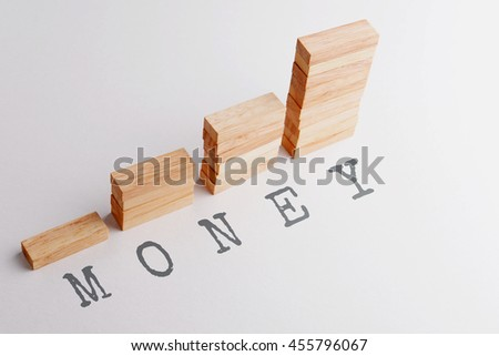 Stack of wood block in statistics graph shape with text MONEY. Business concept in rising and growing money. Selective focus, gray background. - stock photo