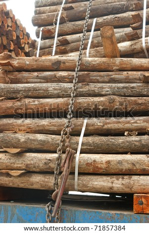 Stack of wood on truck, tied down with chain and steel strips - stock photo