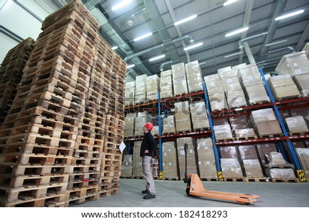 stack of wooden pallets in storehouse - 	worker with hand pallet truck preparing delivery - stock photo