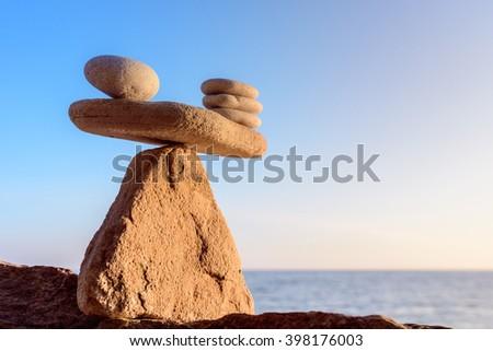 Stack of zen stones in balance on seashore - stock photo