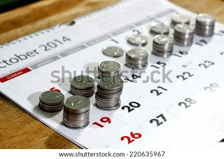 stack or piles of philippine peso coins and a calendar - stock photo