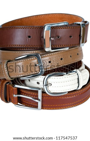 Stack pile of leather belts on white - stock photo