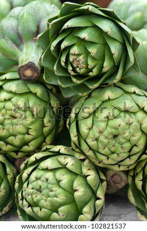 Stacked artichokes for sale at a farmers' market - stock photo