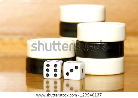 Stacked backgammon black and white pieces and dices - stock photo
