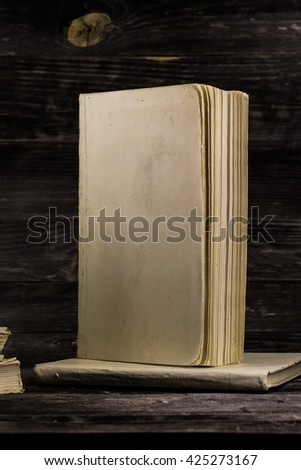 stacked books on a wooden background, place for text - stock photo