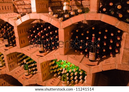 stacked bottles inside a wine cellar - stock photo