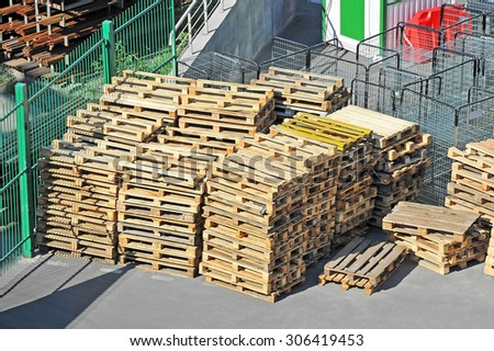 Stacked CEN (EURO) wooden pallets in warehouse - stock photo